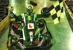 Indoor Karting winner with trophy and chequered flag