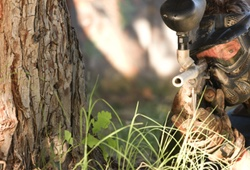 Paintball sniper by a tree