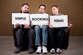 3 men sat on a sofa holding cards up showing simple booking terms